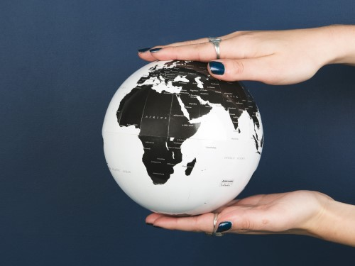 Hands with painted fingernails holding a globe